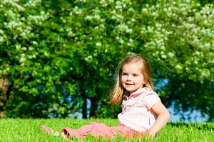 Little Girl Sitting On A Green