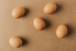 brown eggs scattered on brown carton