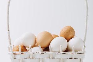 white and brown eggs laying in wicke
