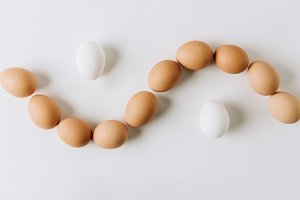 white and brown eggs laying on white