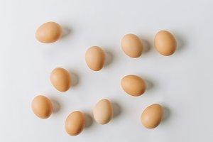 brown eggs scattered on white backgr