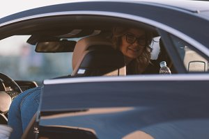 Photo of woman in sunglasses in car