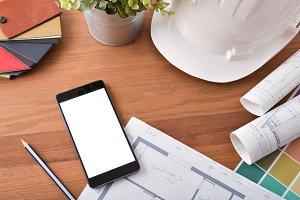 Smartphone on architect's desk