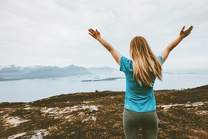 Happy woman raised arms traveling