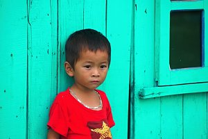 Vietnamese boy leaning against wall