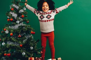 Excited kid standing on gift boxes