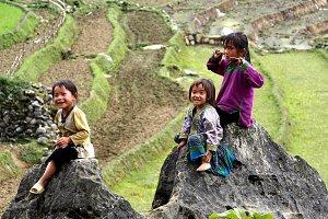 Three little girls sitting on a rock