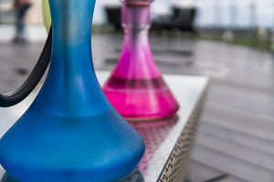 Two colors hookahs on table in