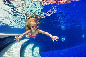 Funny child in goggles dive in pool