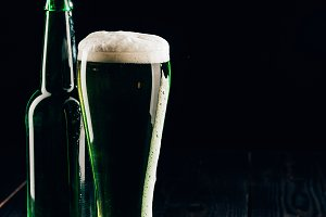 glass and bottle of green beer on wo