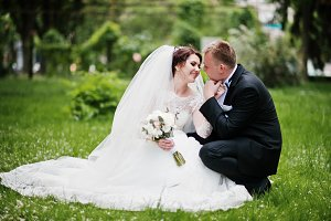 Wedding couple sitting on green gras