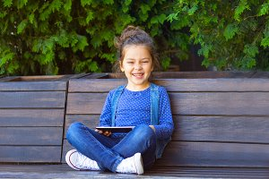 Little girl  play in tablet outdoors