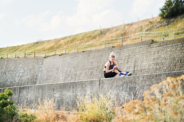 People Stock Photos: HalfPoint - Young sporty woman runner sitting on