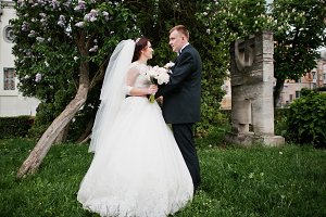 Wedding couple stay near lilac tree
