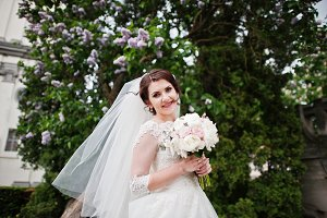 Cute brunette bride under lilac tree