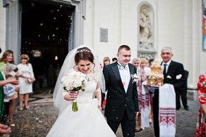 Happy wedding couple walking under c