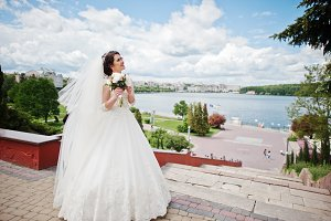 Cheerfull brunette bride against blu