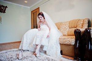 Brunette bride sitting on bed and we
