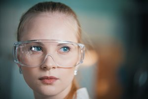 A young woman in work glasses in the