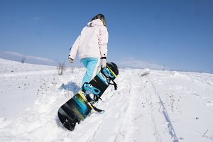 Girl snowboarder with a snowboard on