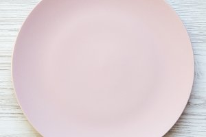 Empty pink plate on a white wooden