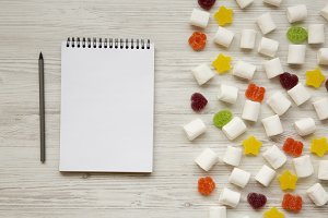 Candy and blank notepad with pencil