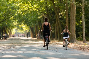 A woman and a girl biking in the par