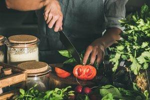 Woman cutting fresh ripe tomatoes on