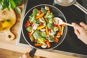 Man cooking fresh vegetables on pan
