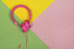 Pink headphone on a colored flat lay