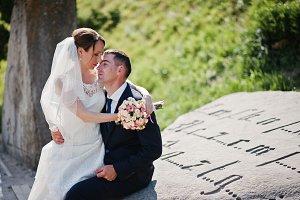 Wedding couple sitting on monument s
