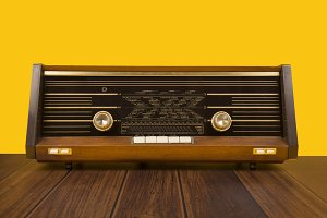 Old antique radio on a yellow backgr
