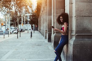 Curly smiling woman with cell phone