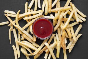 French fries with sauce on a black