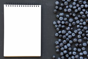 Ripe blueberries with notepad
