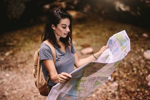 Female hiker in forest reading a map
