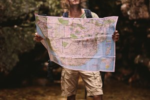 Hiker using a map to find the route