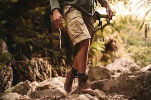 Man in trekking gear hiking on rocky