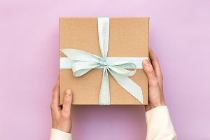 women's hands holding craft gift box