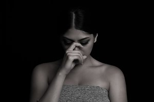Sad woman in black background