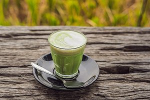 Cup of matcha latte against the old