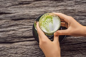 Women's Hand holding cup of matcha