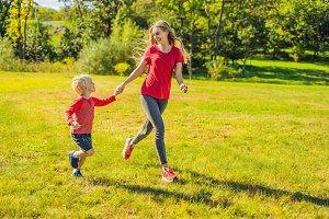 Mom and son run on the green grass