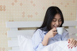 Happy Asian woman drinking coffee