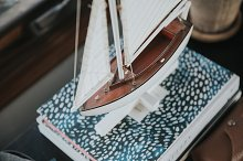 Model boat on books by  in Abstract