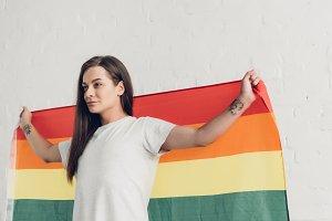 transgender man holding pride flag i