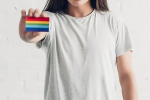 young transgender man holding card w