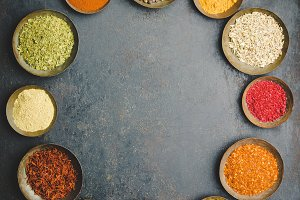 Various bowls of spices over dark ba