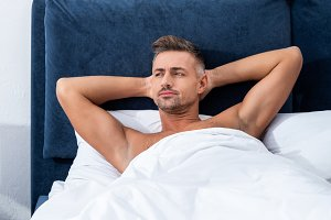 pensive adult man laying in bed and