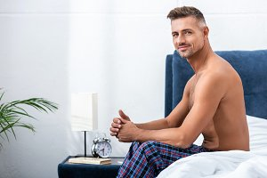 smiling shirtless adult man sitting